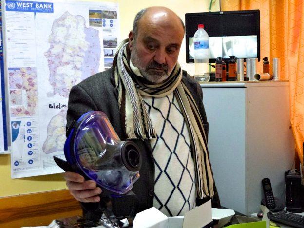 Palestinian headmaster with gas-masks